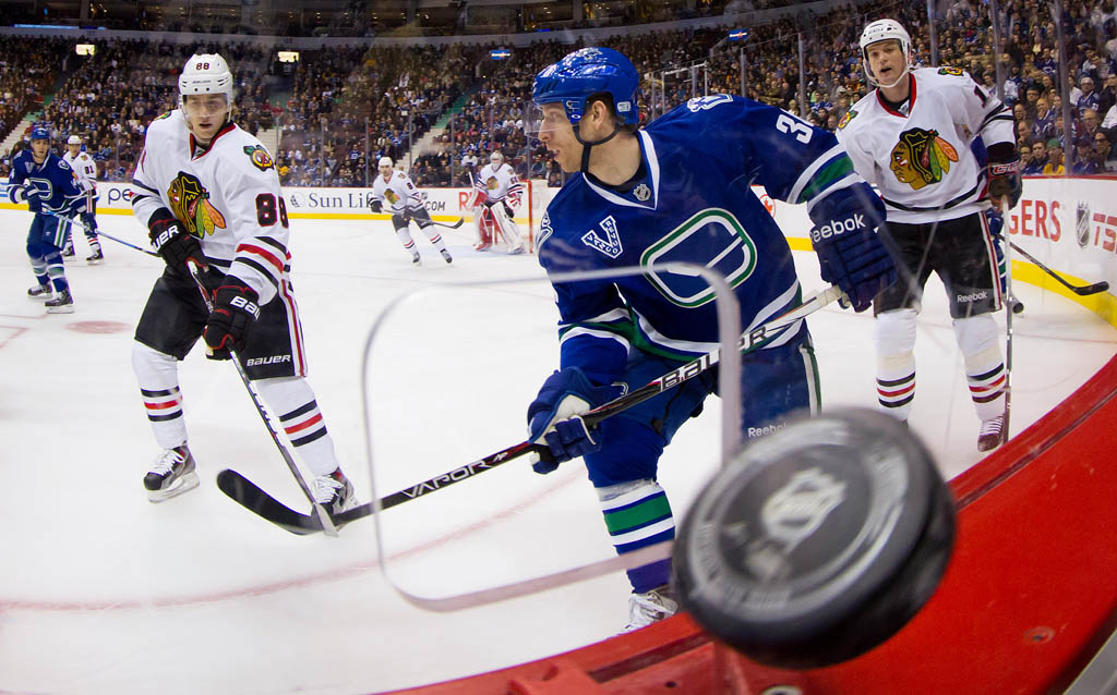 The puck passes through a hole cut in the glass for photographers as Chicago Blackhawks' Patrick Kane, left, Vancouver Canucks' Jannik Hansen, centre, of Denmark, and Chicago's Sheldon Brookbank, right, skate during the first period of an NHL hockey game in Vancouver, B.C., on February Friday 1, 2013. Photo by Darryl Dyck/The Canadian Press