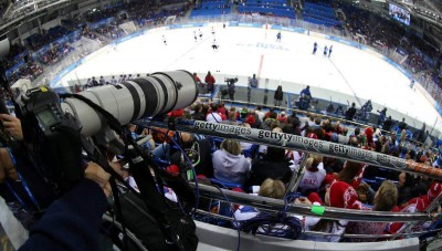 Photographer prepares to shoot an ice hockey game during the Winter Olympics in Sochi.Photo by Bruce Bennett/Getty Images